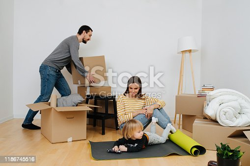 496487362 istock photo Happy family moving to a new home, boy plays with toys while parents unpack 1186745516