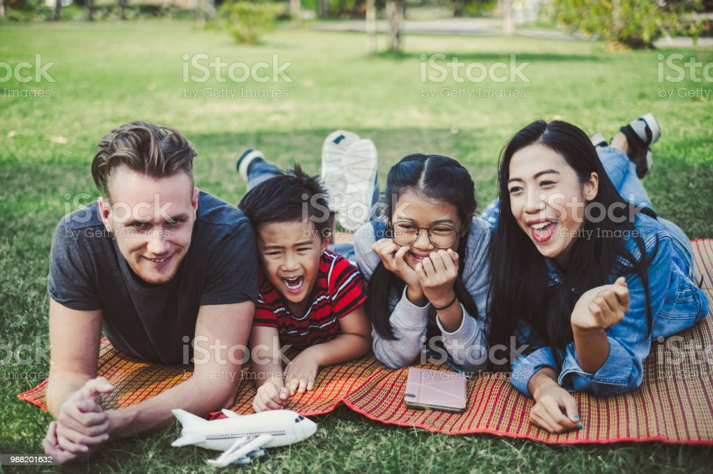 Happy family of Asian and Caucasian laying on garden green park outdoor for playing and relaxing on holiday - Stock image .