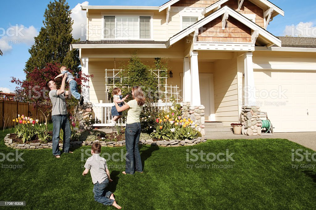 A happy family of five playing in the front yard stock photo