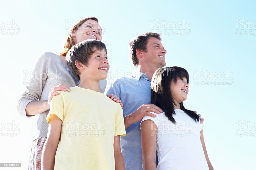 Happy family of four against the clear blue sky royalty-free stock photo