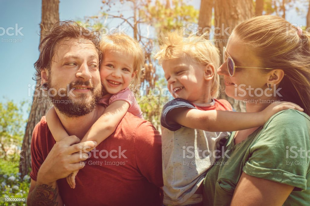 Happy family of four enjoying summer stock photo