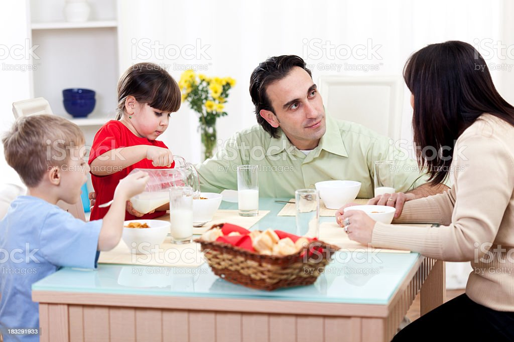 Happy family of four having cereals and milk for breakfast royalty-free stock photo