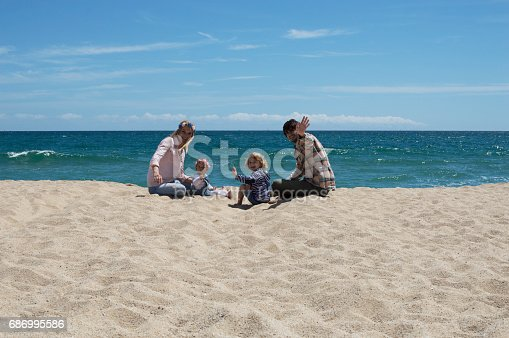 istock Happy family of four on beach vacation 686995586
