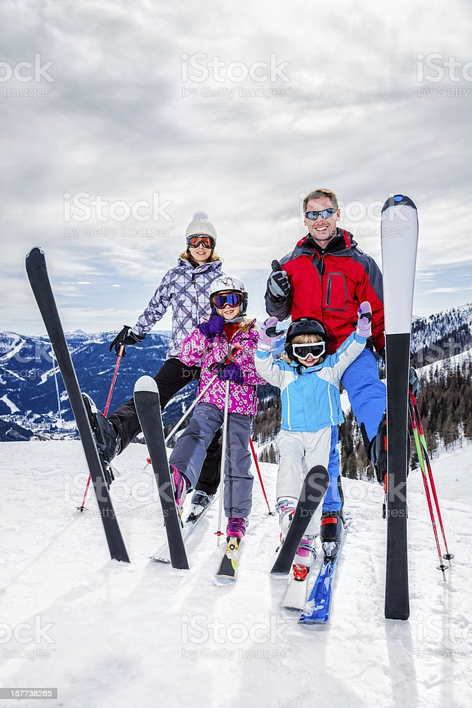 Happy family of skiers on top (of ski resort) royalty-free stock photo