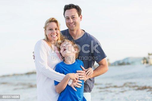 istock Happy family of three on beach 693374696