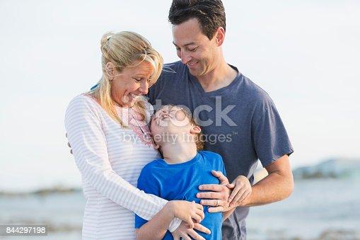 istock Happy family of three on beach 844297198