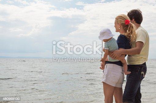 istock Happy family of three on beach vacation 480969100