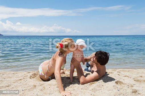 istock Happy family of three on beach vacation 480975298