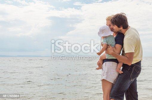 istock Happy family of three on beach vacation 481265664