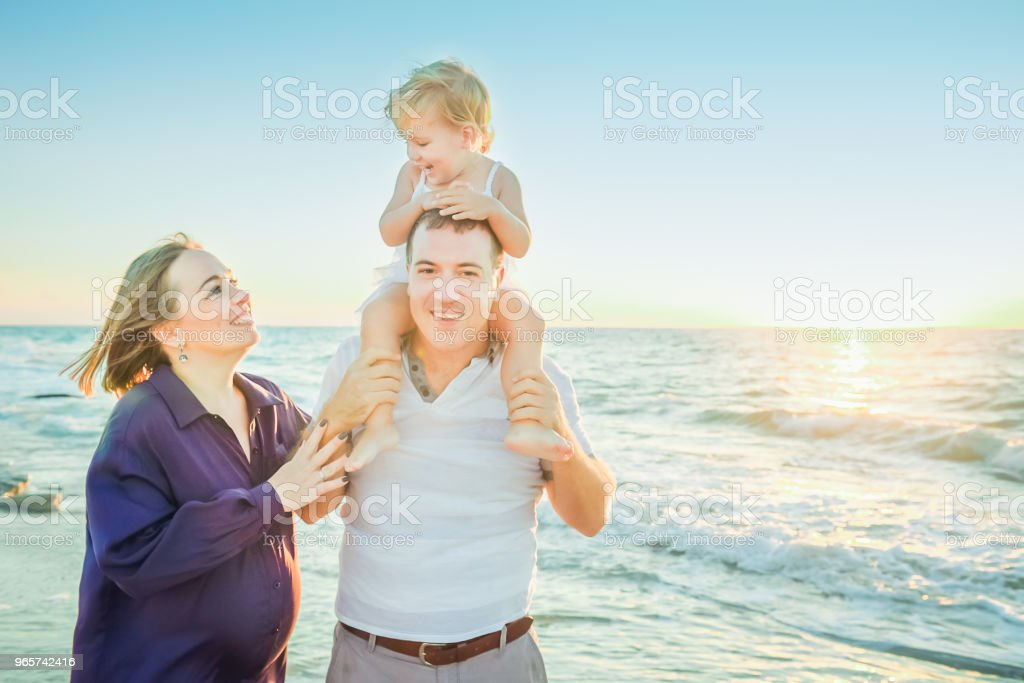 Happy family of three - pregnant mother, father and daughter embracing, laughhing and having fun walking on the beach. Family vacation, travel concept. Backlight, soft selective focus. Copy space. - Royalty-free Adult Stock Photo