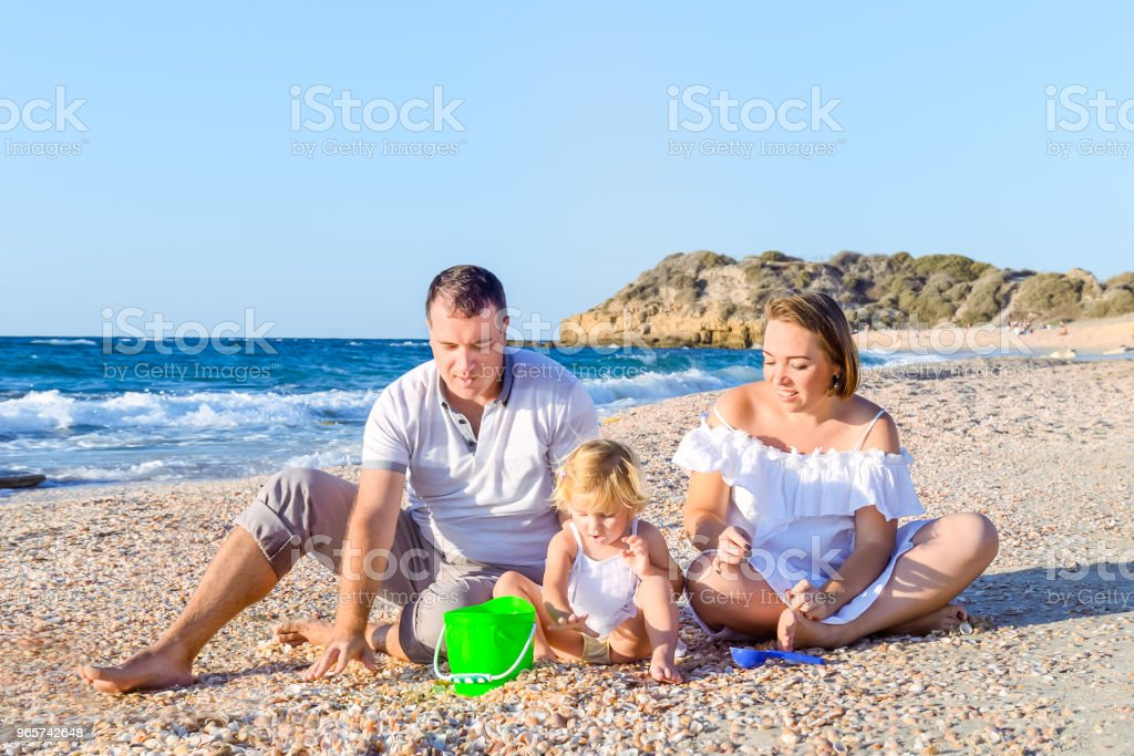 Happy family of three - pregnant mother, father and daughter having fun, playing with sand and shells on the beach. Family vacation, travel concept. Selective focus. Copy space. - Royalty-free Adult Stock Photo
