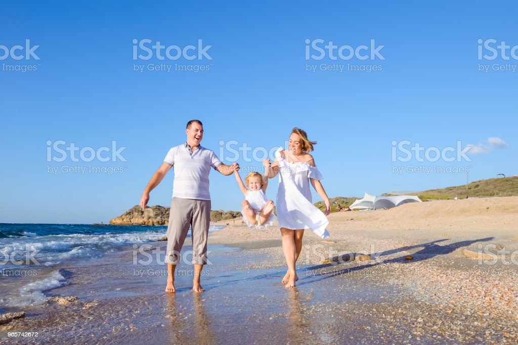 Happy family of three - pregnant mother, father and daughter holding hands and having fun walking on the beach. Family vacation, travel concept. Bright sunlight. Copy space. - Royalty-free Adult Stock Photo