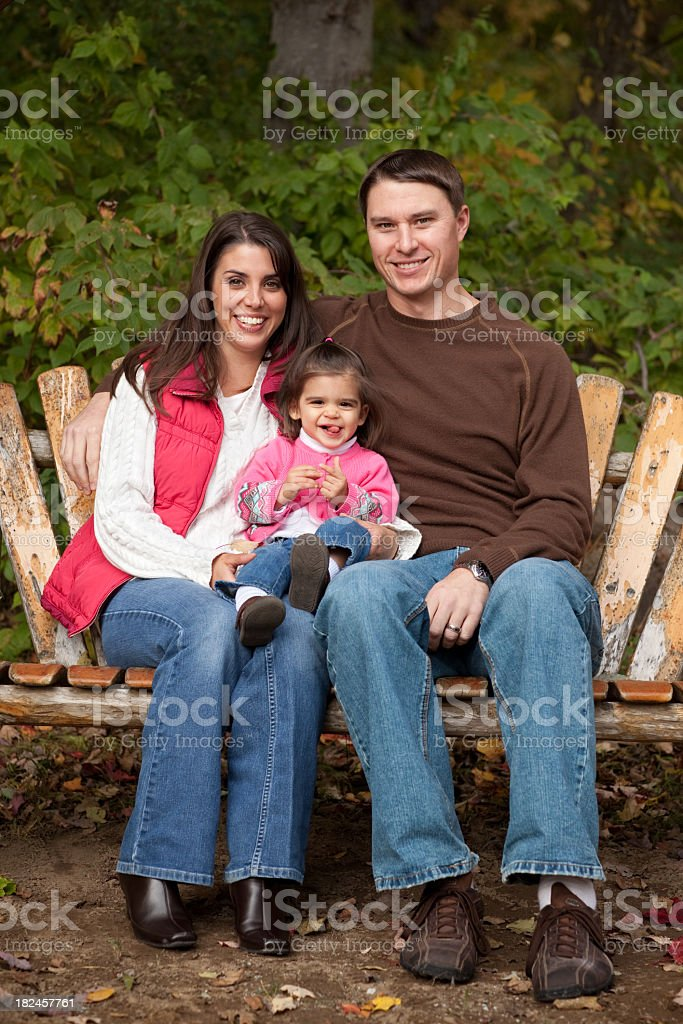 Happy Family of Three Sitting in the Autumn Woods royalty-free stock photo