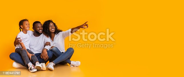 istock Happy family of three sitting on floor and pointing aside 1182441792