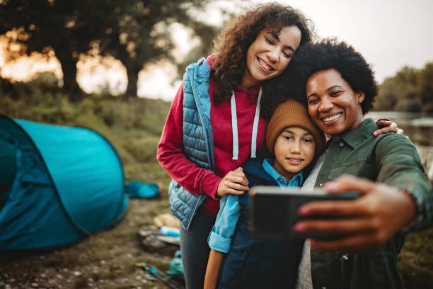 Happy family of three taking selfie near their camping spot stock photo