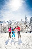 Happy family enjoying their time on a ski trip, skiing and having fun on a snowy mountain