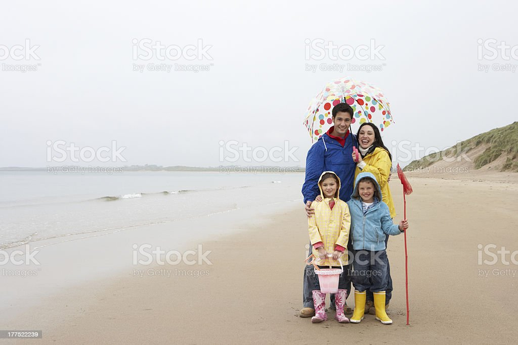 Happy family on beach with umbrella stock photo
