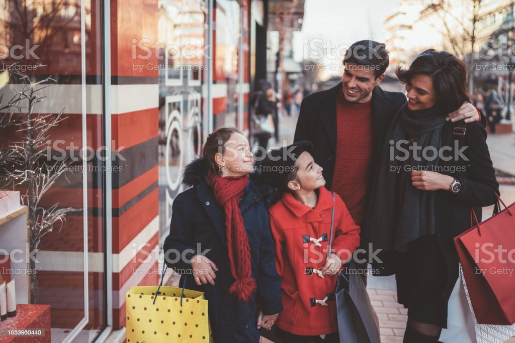 Smiling family with two daughters outside at Christmas shopping