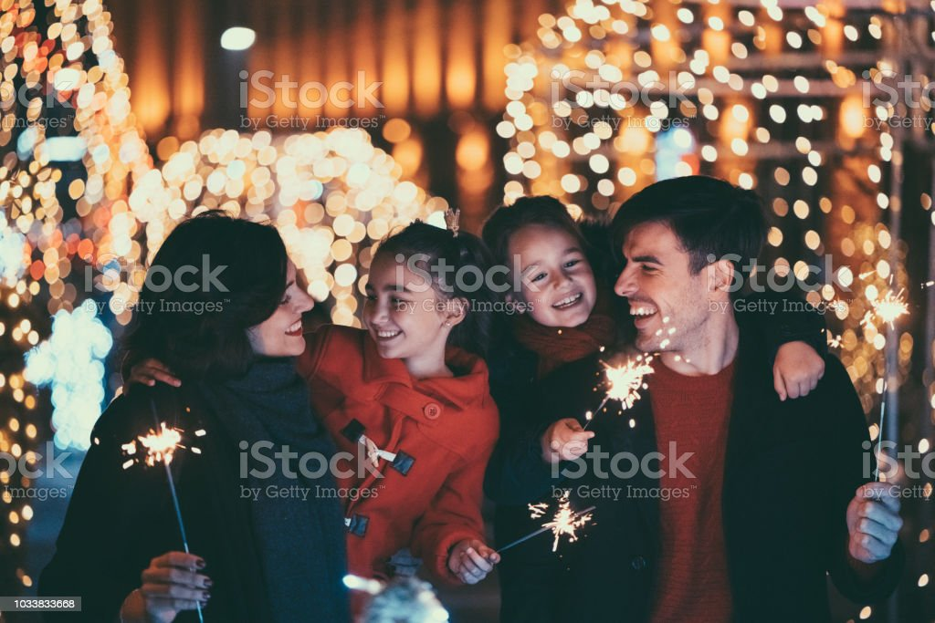 Happy family on Christmas with burning sparklers stock photo