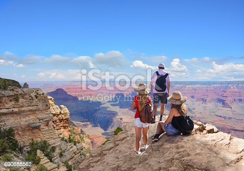 Family hiking on vacation,Family with arms raised standing on top of the mountain, looking at beautiful summer mountains landscape. Grand Canyon National Park, Arizona, USA.