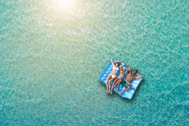 gelukkige familie op opblaasbaar vlot op de zee - strandvakantie stockfoto's en -beelden