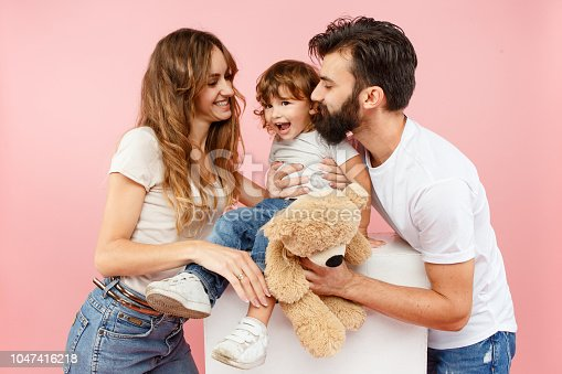 istock A happy family on pink background 1047416218