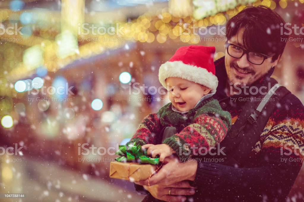 Cute baby boy and his father enjoying Christmas shopping