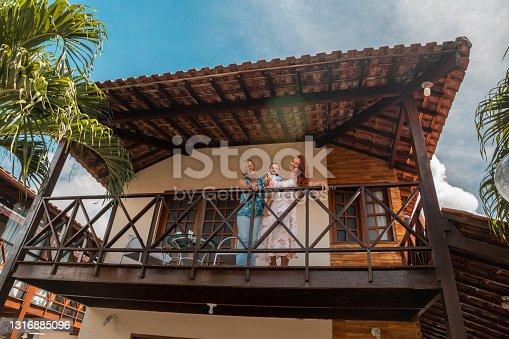 istock Happy family on the balcony at the summerhouse 1316885096