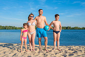 Happy family on the beach by the river. Lifestyle. Sports games on a sunny day.
