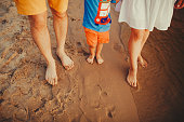 Happy family on the beach. Closeup of family feet with boy baby walking on sand. Man and woman holding their baby. Walk by the river. Travel lifestyle, parents with kids on summer vacation.