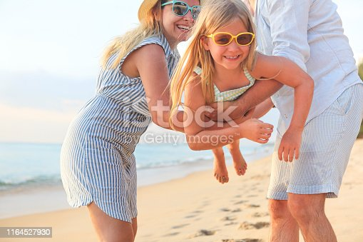 147878016 istock photo Happy family on the beach. People having fun on summer vacation. Father, mother and child against blue sea and beach background 1164527930