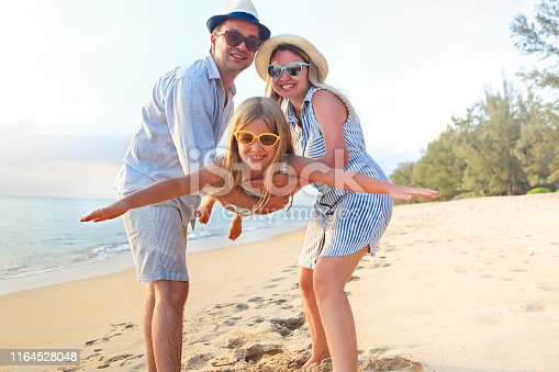 147878016 istock photo Happy family on the beach. People having fun on summer vacation. Father, mother and child against blue sea and beach background. 1164528048