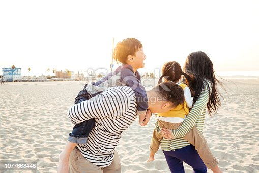 istock Happy family on the beach 1077663448