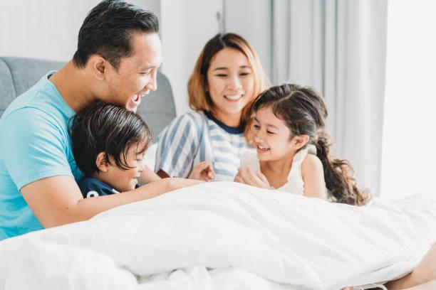 happy family on the bed together - cultura orientale foto e immagini stock