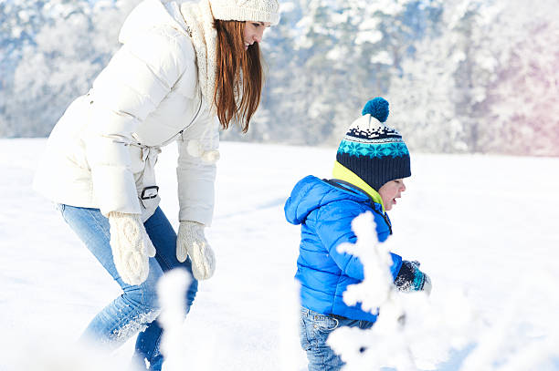 Happy family on the walk in sunny, snowy day stock photo