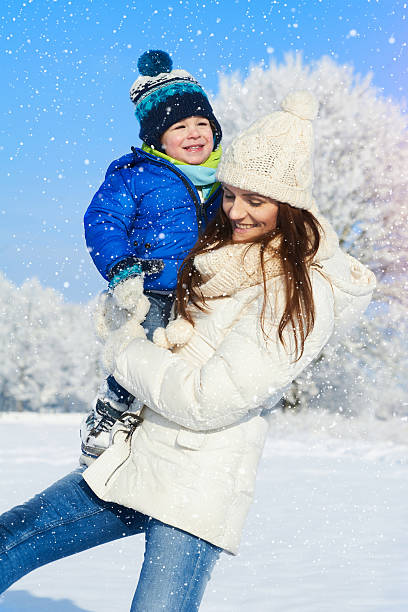 Happy family on the walk in sunny, snowy, winter day stock photo
