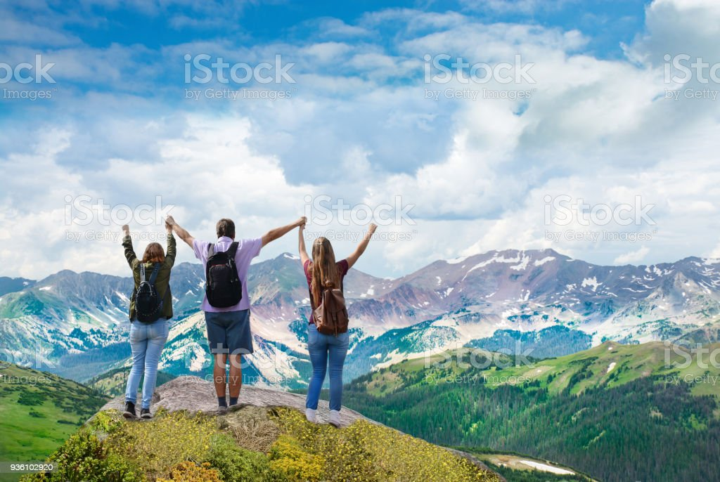 Happy family on top of beautiful mountain holding raised hands. stock photo