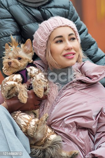 Happy family on walk with their funny terrier. Little dog with stylish hipster mom and son spend time outdoors playing and having fun. Lifestyle portrait. Love between pet and owner. Family time
