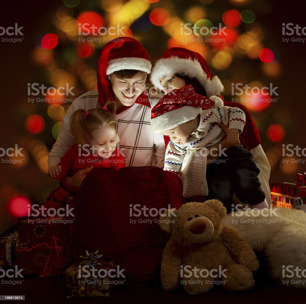 Happy family opening lighting bag with gifts royalty-free stock photo