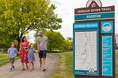 This family is enjoying their time together near the Jordan River Trail in northern Utah. The family consists of mother, father, son and daughter.  Visible in the photo is a sign showing directions for the trail in a public park.  This shot was taken  in Riverton Utah near the entrance to the trail in June of 2019.