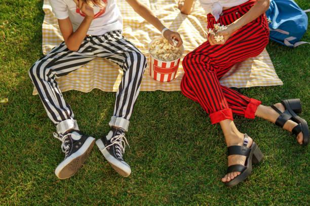glückliche familie im freien spaß essen popcorn - mensch isst gras stock-fotos und bilder