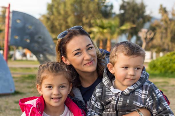 Glückliche Familie im Freien. Mutter mit zwei Kleinkindern. – Foto