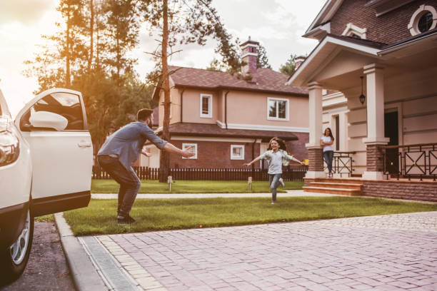 Happy family outdoors Happy family. Dad came home, daughter is running to meet him while wife is waiting on the house's porch. car stock pictures, royalty-free photos & images