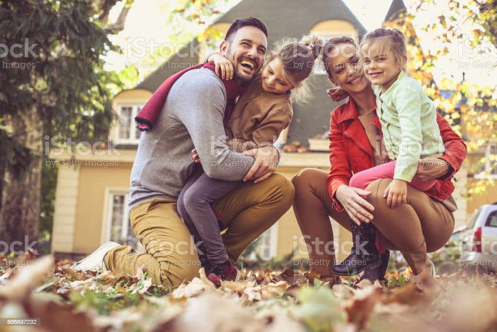 Happy family outside in colorful fall backyard poses to camera. stock photo