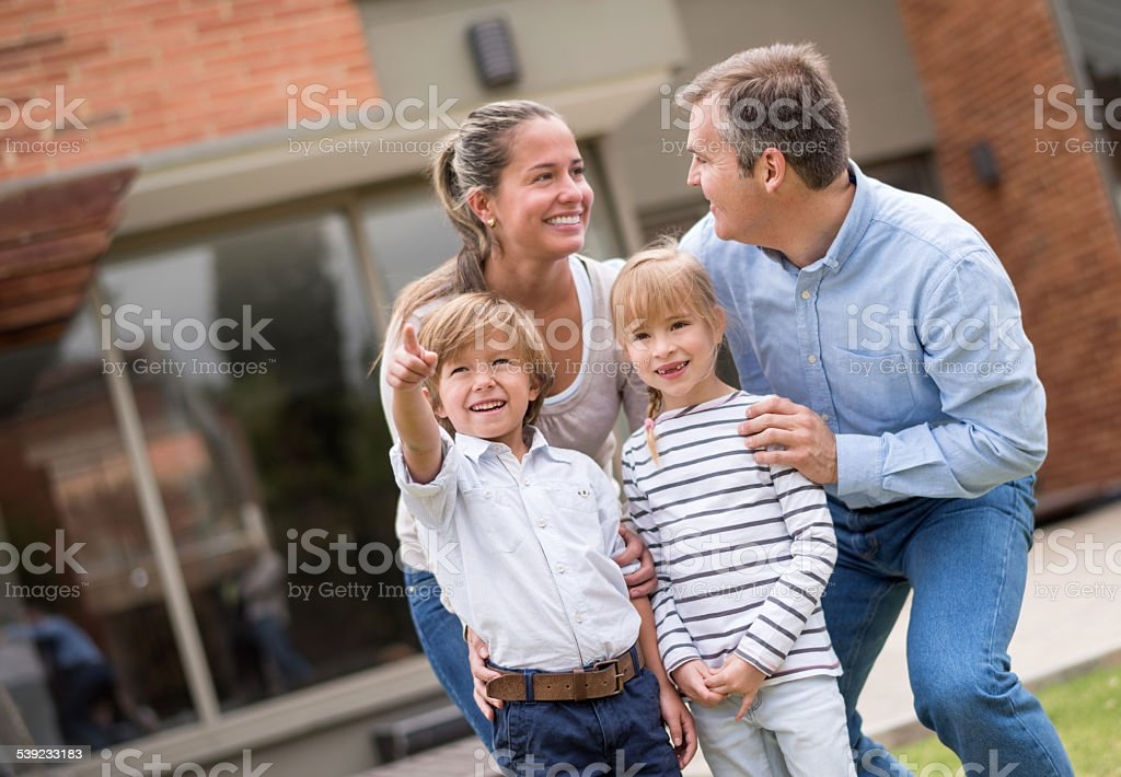 Happy family outside their house royalty-free stock photo