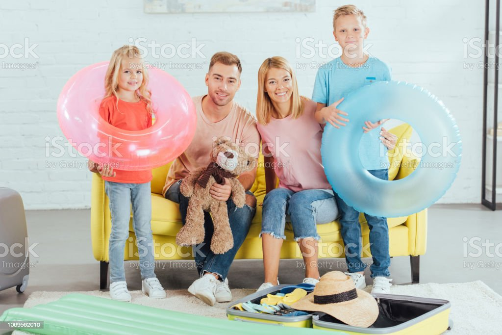 happy family packing baggage for summer vacation, travel concept stock photo