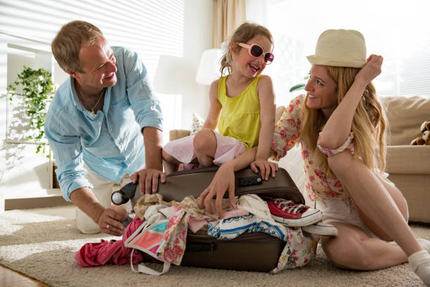 Happy family packing suitcase. stock photo