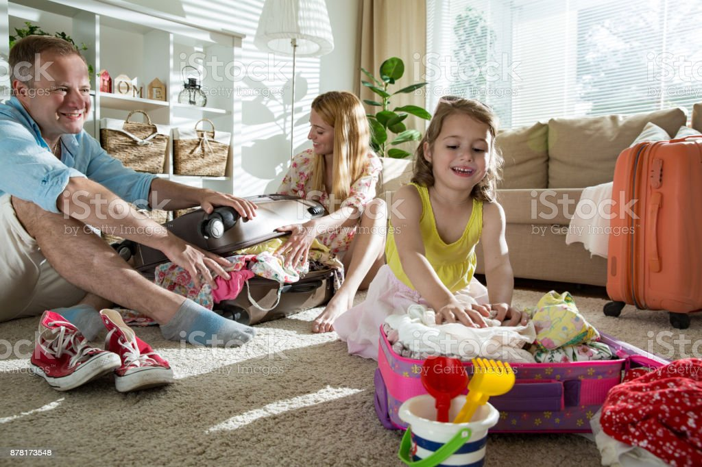 Happy family packing suitcase stock photo