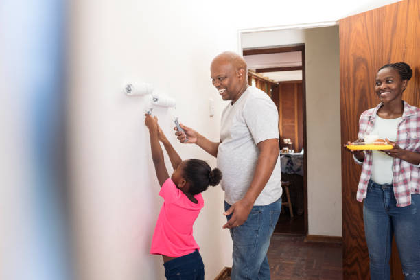 Happy family painting a room together stock photo