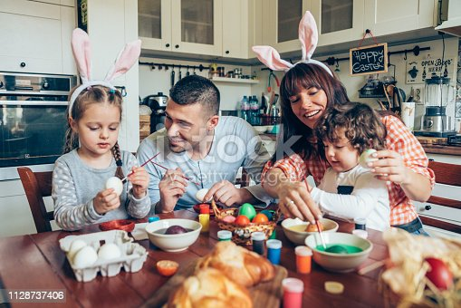 istock Happy family painting Easter eggs 1128737406